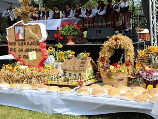 Wieńce dożynkowe ustawione na stole; przed nimi chleby