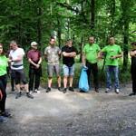 Grupa ludzi (część w zielonych koszulkach z napisem Leszy, z niebieskimi workami przygotowuje się do wyjścia do lasu