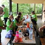 Uczestnicy akcji siedzą przy stole i posilają się ciastem