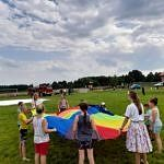 Dzieci bawiące się przy kolorowej tęczowej płachcie