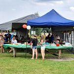 Stoły i namioty piknikowe a przy nich luszie