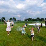Dzieci na łące puszczające bńki mydlane