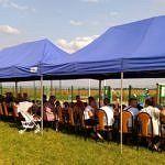 Piknik przy DL w Glinie - mieszkańcybiesiadują przy stołach pod namiotami
