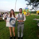 Sołtys wsi z dziewczyną, która trzyma nagrodę - wiatrak