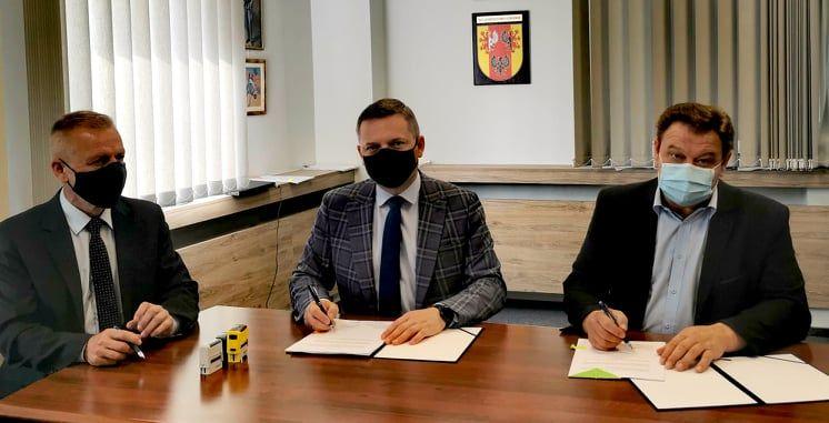 Trzej mężczyźni w maseczkach przy stole podpisują umowę