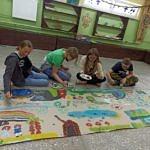 Dzieci malują wspólnie duży rysunek