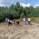 Dzieci ćwiczą w lesie, na piachu