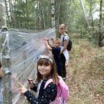 Dzieci malują na folii rozciągniętej wśród drzew