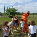 Dzieci przy dmuchanym pomarańczowym smoku