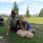 Starszy chłopak uczy dzieci masażu serca na fantomie