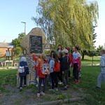 Grupa dzieci przed pomnikiem w Woli Krzysztoporskiej