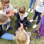 Dzieci siedzą na trawie w kręgu