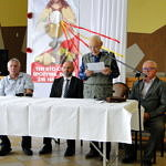 Kilka osób przy stole pokrytym białym obrusem. Starszy człowiek czyta coś z kartki