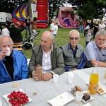 Mieszkańcy podczas pikniku siedzą przy stole z ciastami