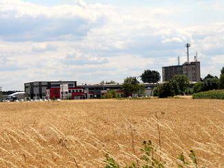 zboże na polu, a w tle zakład przemysłowy