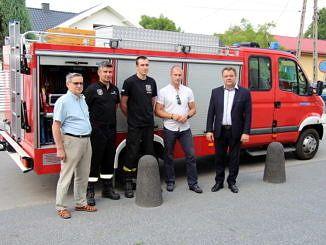 Nowy samochód strażacki a przed nim predstawiciele strażaków i wót gminy