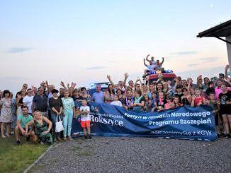 Zdjęcie zbiorowe uczestników festynu z banerem informacyjnym