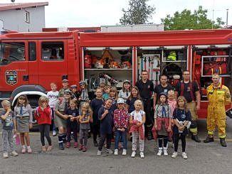 Zdjęcie zbiorowe dzieci i strażaków przed wozem strażackim