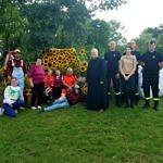 zdjęcie zbiorowe mieszkańcy z księdzem i strażakami