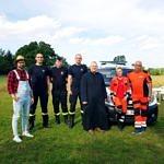sołtys w kapeluszu, strażacy, ksiądz i ratownicy medyczniz