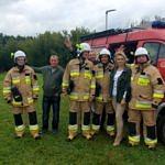 Strażacy w mundurach przy samochodzie z sołys Kamilą Kaczorowską