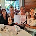 Cztery kobiety siedza przy stole ze statuetką i dyplomem