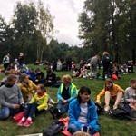 Uczestnicy odpoczywają na łące pod pomnikiem na Górach Borowskich