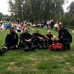 Uczestnicy odpoczywają na łące pod pomnikiem na Górach Borowskich - na pierwszym planie pięcioro strażaków