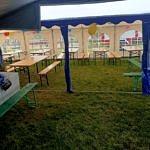 Drewniane stoły i ławki pod białym namiotem