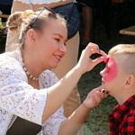 Kobieta maluje twarz chłopca
