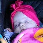 Malutka dziewczynka w różowej czapeczce w wózku