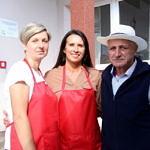 Dwie kobiety w czerwonych fartuchach i mężczyzna w kapeluszu