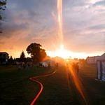 rozciągnięty wąż strażacki i przeświecające promienie słońca