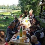 Młodzi wędkarze podczas posiłku przy stawie