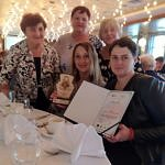 Pięć kobiet siedzi przy stole ze statuetka i dyplomem
