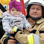 Strażak z małym dzieckim na rękach