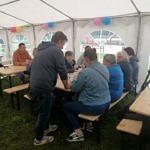 Mieszkańcy pod namiotem przy stole z przekąskami