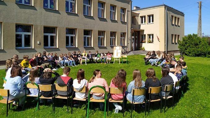 Dzieci siedzą w kręgu przed szkołą na krzesłach ustawionych na trawie - obok tablica z hasłami Narodowego Czytania