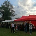 Plac boisko z rozstawionymi namiotami i ludzie przed nimi