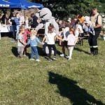Małe dzieci tańczą w kółku z żywa maskotką