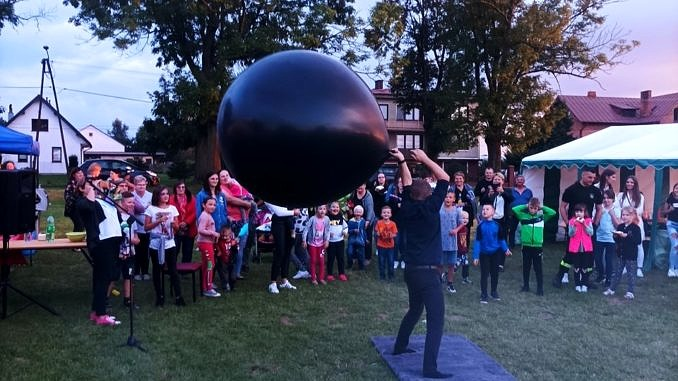 Tłum ludzi i pokazy - człowiek z wielkim czarnym balonem