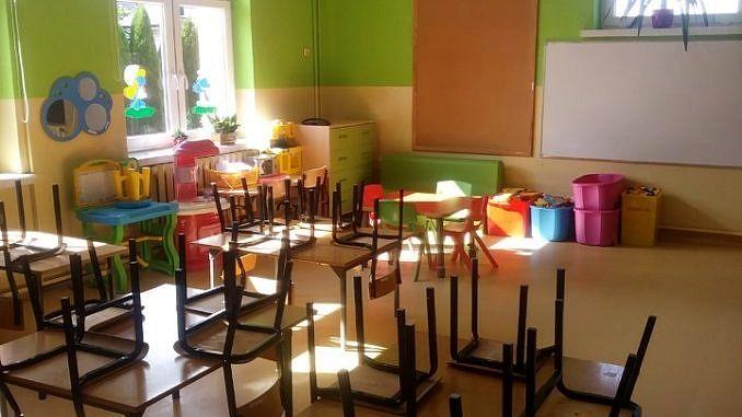 Kolorowa klasa szkolna po odmalowaniu ścian na zielono; ławki szkolne i zawieszone na nich krzesełka