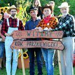 Czterej sołtysi w kapeluszach i kraciastych koszulach przy wykonanym na drewnie napisie witamy, KGW Parniewiczki