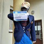 Kukła mężczyzny z plakatem informującym o szczepieniu