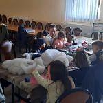 Dzieci przy stole z materiałami plastycznymi podczas warsztatów