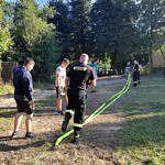 Strżacy rozciągają węże