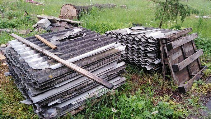 Na dwóch stertach leżą elementy eternitu azbestowego