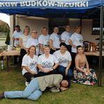 Członkinie KGW w białych koszulkach z napisem KGW i motywem ludowym przed nimi leży mężczyzna w kapeluszu