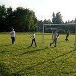 Dzieci grają w piłkę nożną na boisku