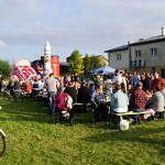 Dużo mieszkńców podczas pikniku - jedni siedza na ławkach, inni stoją